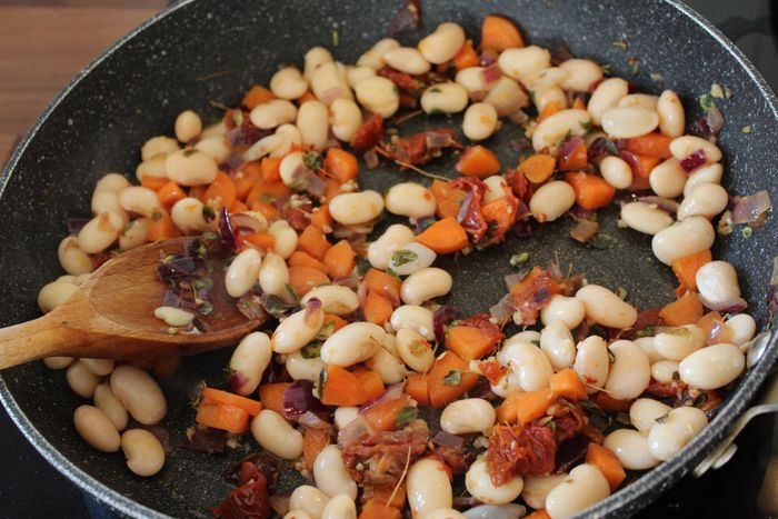 cooking carrots, onion, butter beans, sundried tomatoes and herbs